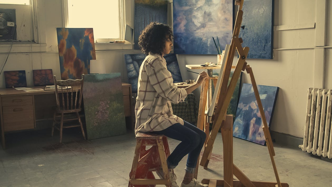 A college student painting to sell and make money from her artwork